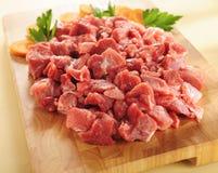 Raw beef stew. Arrangement on a cutting board. Raw beef stew on a wooden cutting board royalty free stock photos