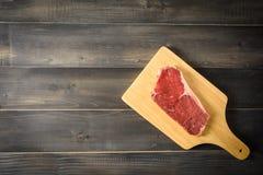 Raw beef striploin steak on cutting board Stock Image