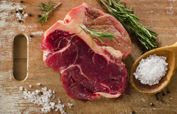 Raw beef t-bone steak on a old wooden board Stock Photography