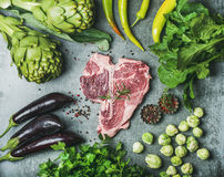 Raw beef t-bone steak with vegetables and spices, concrete background. Ingredients for healthy protein rich meat dinner. Fresh raw beef uncooked t-bone steak Stock Photo