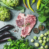 Raw beef t-bone steak with vegetables and spices, square crop. Ingredients for healthy protein rich meat dinner. Fresh raw beef uncooked t-bone steak with green Royalty Free Stock Photo