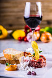 Raw beef .Tasty Steak tartare. Classic steak tartare on white plate with egg bread and cup red wine Royalty Free Stock Photography