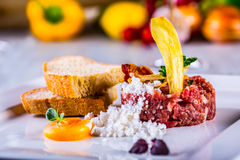 Raw beef .Tasty Steak tartare. Classic steak tartare on white plate with egg bread and cup red wine Stock Photos