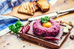 Raw beef .Tasty Steak tartare. Classic steak tartare on wooden b Stock Image