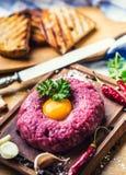 Raw beef .Tasty Steak tartare. Classic steak tartare on wooden b Stock Photo