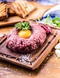 Raw beef .Tasty Steak tartare. Classic steak tartare on wooden b Stock Photos