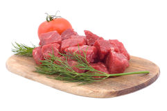 Raw beef with tomato and dill. On a wooden hardboard isolated on white Royalty Free Stock Image