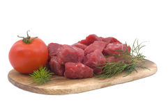 Raw beef with tomato and dill. On a wooden hardboard isolated on white Royalty Free Stock Photos