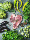 Raw beef uncooked t-bone steak with green vegetables and spices. Ingredients for healthy protein rich meat dinner. Fresh raw beef uncooked t-bone steak with Royalty Free Stock Image
