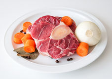 Raw beef and vegetables. A chop of raw beef with carrots and peeled onion Stock Images