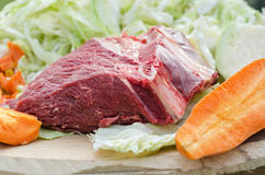 Raw beef and vegetables, ingredients for cooking. A big piece of raw beef and vegetables on a rough Board, ingredients for cooking at the picnic Stock Photo