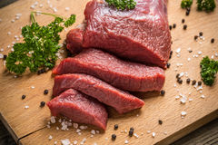 Raw beef. On wooden cutting board with parsley, pepper and salt Stock Photography