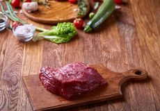 Raw beefsteak on cutting board with vegetables and seasoning, selective focus, close-up, top view. Raw beefsteak on cutting board with rosemary, spicies, garlic Royalty Free Stock Image