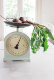 Raw beetroot vegetables with leaves on vintage scales in a conte. Raw beetroot vegetables with leaves on vintage scales in a light bright contemporary home Royalty Free Stock Photography