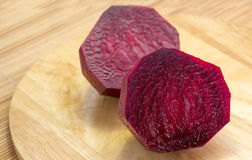 Raw beets cut in half. Raw beets on a wooden board Royalty Free Stock Image