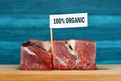 Raw big meat chunks on wooden plate with label saying `100 percent porganic`, concept for healthy organic food production royalty free stock photography