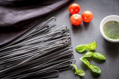 Raw black pasta with basil and tomatoes Royalty Free Stock Image