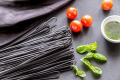 Raw black pasta with basil and tomatoes Royalty Free Stock Images