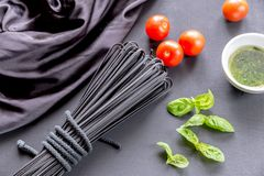 Raw black pasta with basil and tomatoes Stock Images