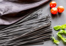 Raw black pasta with basil and tomatoes Royalty Free Stock Photography