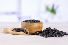 Raw black turtle beans with red tulips stock images