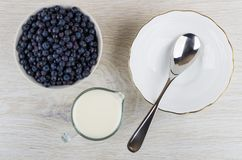 Raw blueberry in bowl, jug of milk, spoon in bowl Royalty Free Stock Photo