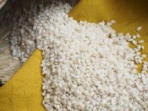 Raw bomba white rice. On yellow Royalty Free Stock Photography