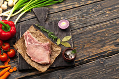 Raw bone steak on paper with vegetables. Raw bone steak on paper on a dark wooden background with vegetables, top view with copy space Royalty Free Stock Photos