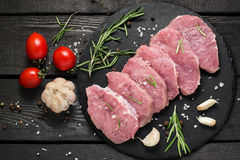 Raw boneless pork chops, vegetables, herbs and spices. Fresh uncooked boneless pork chops on a slate plate, vegetables, herbs and spices on a dark wooden Stock Images