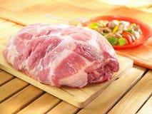 Raw boneless shoulder square cut on a wooden cutting board. Raw boneless shoulder square cut on a wooden cutting board and wooden table Stock Photos