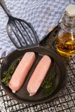 Raw british sausages with herbs in a cast iron pan Stock Photos