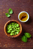 Raw broad beans end olive oil. On wooden Stock Image