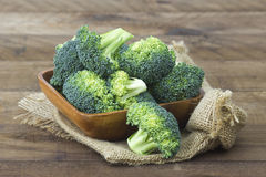 Raw broccoli in a bowl. On wooden background Stock Photo