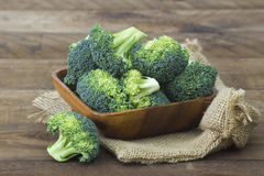 Raw broccoli in a bowl. On wooden background Stock Images
