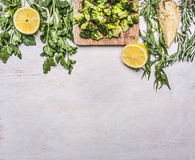 Raw broccoli in a cutting board with herbs, lemon, celery root border ,place for text wooden rustic background top view close. Raw broccoli in a cutting board Stock Image