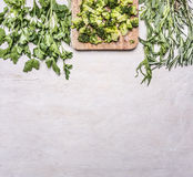 Raw broccoli on a cutting board with rosemary, parsley and herbs border ,place for text wooden rustic background top view close Royalty Free Stock Image
