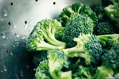 Raw broccoli florets, wet in metal colander, washed. And in size bites Stock Image