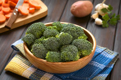 Raw Broccoli. Fresh raw broccoli florets in wooden bowl with carrot slices on wooden board, potato, garlic and parsley in the back, photographed on dark wood Royalty Free Stock Photography