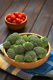Raw Broccoli. Fresh raw broccoli florets in wooden bowl with cherry tomatoes in the back, photographed on dark wood with natural light (Selective Focus, Focus Stock Images