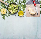 Raw broccoli in a pan with herbs, lemon, celery root on a cutting board with a knife border ,place text on wooden rustic backg Royalty Free Stock Image