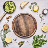 Raw broccoli in a small frying pan, parsley, oil, salt, lemon, pickles laid out around  cutting board place for text,frame on woo Royalty Free Stock Images