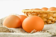 Raw brown chicken eggs in a basket on burlap on a white wooden table. Ingredients for cooking. Raw brown chicken eggs in a basket on burlap on a white wooden Stock Image