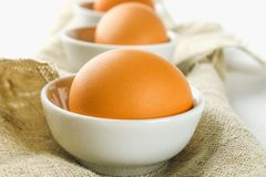 Raw brown chicken eggs in glass bowls on a white wooden table. Ingredients for cooking. Raw brown chicken eggs in glass bowls on a white wooden table Royalty Free Stock Images