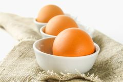 Raw brown chicken eggs in glass bowls on a white wooden table. Ingredients for cooking. Raw brown chicken eggs in glass bowls on a white wooden table Stock Image