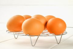 Raw brown chicken eggs on an iron grate on a white wooden table. Ingredients for cooking. Raw brown chicken eggs on an iron grate on a white wooden table Royalty Free Stock Image
