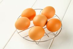Raw brown chicken eggs on an iron grate on a white wooden table. Ingredients for cooking. Raw brown chicken eggs on an iron grate on a white wooden table Royalty Free Stock Photos