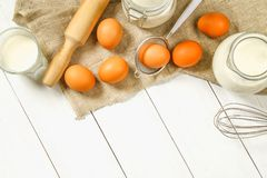Raw brown chicken eggs, milk, sugar, flour, whisk, rolling pin on a white wooden table. Ingredients for cooking. Raw brown chicken eggs, milk, sugar, flour Royalty Free Stock Image
