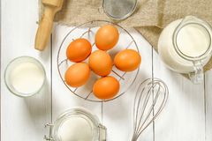 Raw brown chicken eggs, milk, sugar, flour, whisk, rolling pin on a white wooden table. Ingredients for cooking. Raw brown chicken eggs, milk, sugar, flour Royalty Free Stock Photos