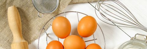 Raw brown chicken eggs, milk, sugar, flour, whisk, rolling pin on a white wooden table. Ingredients for cooking. Raw brown chicken eggs, milk, sugar, flour stock images