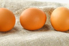 Raw brown chicken eggs in one row on burlap on a white wooden table. Ingredients for cooking. Raw brown chicken eggs in one row on burlap on a white wooden Stock Image